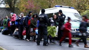 Migrants are cleared by German police officers after crossing the Austrian border.