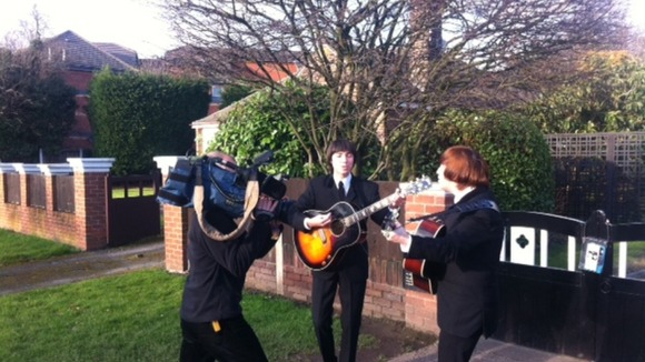 ITN Cameraman Keith Edwards films a Beatles tribute act outside the newly listed building in Liverpool