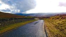 looking down a freshly gritted road, mountains in background, green verges either side
