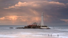 misty St Mary's Lighthouse, sea and mist tinged orange, misty swirls