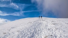 two people in the distance walking away from the camera up a snowy mountain