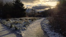 frosty snowy path dividing into two, sun setting