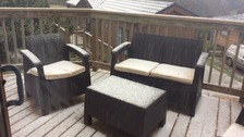 garden furniture in a sleet and snow shower, covered in a thin layer of snow
