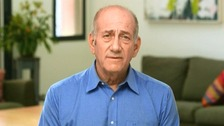 Ehud Olmert, who appeared in a blue shirt in his video plea, will wear a prison uniform and have two cellmates but will be segregated from the general prison population for security reasons.