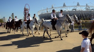 Mounted police officers ride past the Olympic stadium in the Olympic Park, during the Paralympic Games in London.