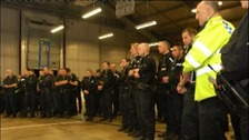 Police photo of officers being briefed before early morning raids