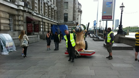 A Mandeville statue is wheeled away from its position on the South Bank.