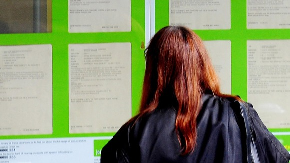 A woman looking into the window of a job centre.