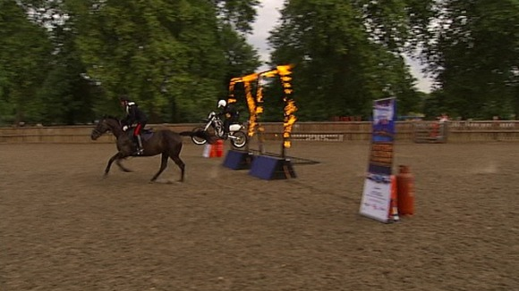 A horse from the Household Cavalry beats a motorcycle from the Royal Signals White Helmets in a race through a flaming hoop.