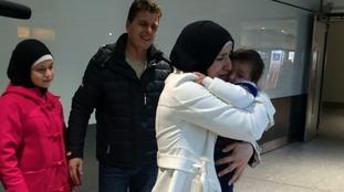 Rajaa Al Sharki cuddling her son