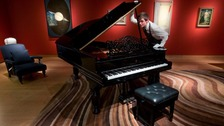 A member of Christie's with Sting's Steinway piano.