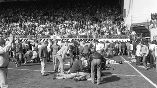 Fans on the pitch receiving attention after severe crushing at Hillsborough