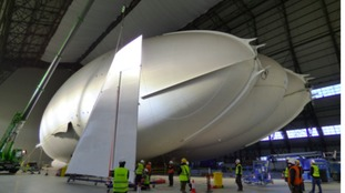 A crane lifts the fin from the hangar floor