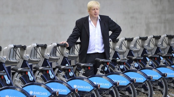 Boris standing next to Barclays bikes
