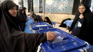 A woman casts her ballot in Tehran today