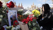 A woman leaves flowers at the bridge where Mr Nemtsov was shot