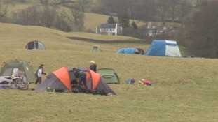 The early arrivals begin pitching their tents.