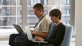 Two people typing on laptops.