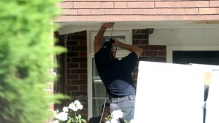 Police use a fibre optic camera as they search outside the home of Saad al-Halli in Claygate, Surrey.