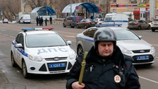 A Russian police officer stands at the site where a woman suspected of murdering a child was detained in Moscow, Russia