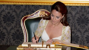 The Duchess of Cambridge signs a special book at the residence of Malaysia's king.
