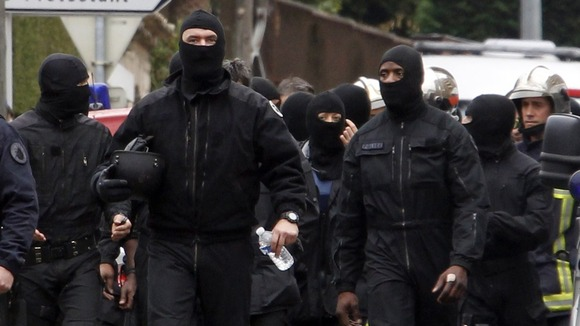 Masked French special unit policemen leave the scene after the assault to capture gunman Mohamed Merah