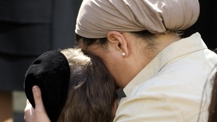 A teacher comforts a child as they observe a minute of silence at a Jewish school
