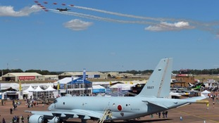 The Red Arrows flank the Vulcan above the crowds