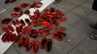 Red shoes in People stand beside a group of red shoes used for a performance to denounce violence against women organized by Amnesty International during International Women's Day in Gijon, Spain