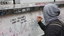 A fan writes on a wall on Abbey Road in a tribute to 'fifth Beatle' George Martin