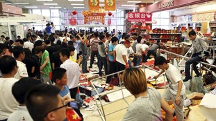 Demonstrators damage a Japanese-funded shopping center during a protest in Qingdao