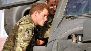 Prince Harry examines the cockpit of an Apache helicopter