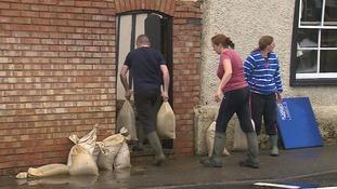 People use sandbags as makeshift flood defences.