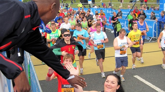 Mo Farah, who was acting as honorary starter, high fives runners during the start of the Great North Run in Newcastle.
