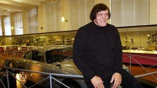 Richard Kiel, who played 'Jaws' in James Bond movies, poses with an Aston Martin