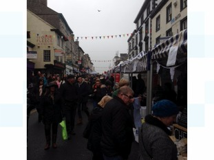 A busy street filled with people and stalls at Kendal festival of food