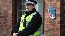 A police officer outside the house in Dalgety Bay in Fife