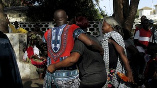 People comfort each other at the scene of the attack in the Ivory Coast
