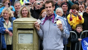 Andy Murray standing next to his gold painted post box during a walkabout in Dunblane