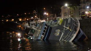 Storm damaged trawler remains capsized in harbour