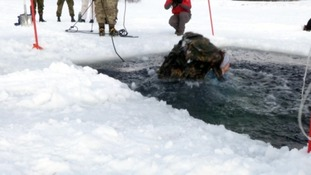 One solider paddling in the ice cold water after jumping in.