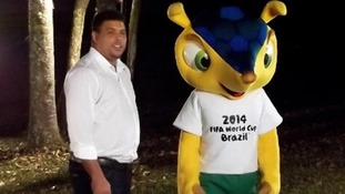 The mascot carries the colors of the Brazilian flag