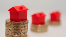 Toy houses on pound coins