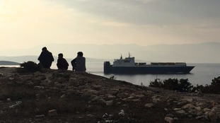 Refugees gaze across the water to the Greece