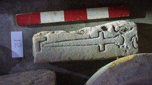a fragment of a Medieval cross slab carved with a small  sword, measuring 43cm x 13cm.