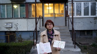 Ajsa Pekez, mother of 11-year-old girl Tina, poses with her daughter's drawings at the place where she was killed, in Sarajevo September 1, 1992.