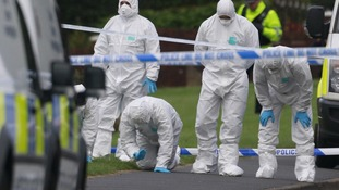 Police forensic officers search the scene of a shooting in Hattersley