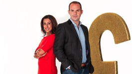 Saira Khan and Martin Lewis standing next to a huge Gold pound sign, an oversize pound coin and a knee high credit card. 