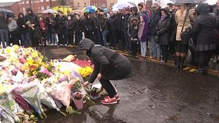 A well-wisher leaves flowers at a vigil for Glasgow shopkeeper Asad Shah