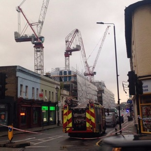Crane bent over double in high winds in Greenwich.